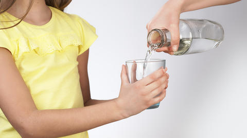 Mom pours water into a little girl's glass. little girl pours water into a glass Live Action
