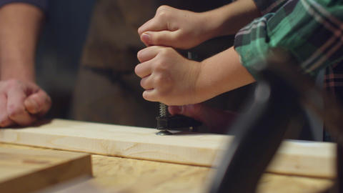 The boy tries to clamp a wooden board in a vice Live Action