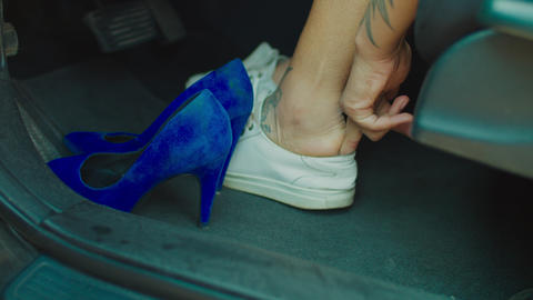 Female driver changing high heels to comfortable shoes Live Action