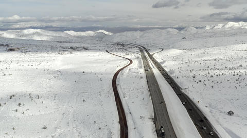 Aerial, drone, overlooking traffic, surrounded by snowy peaks, on a winter day Live Action