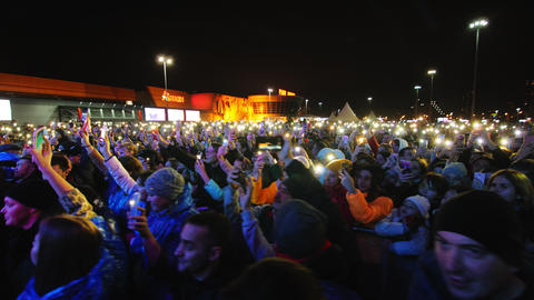 crowd with cellphones watches musical show in winter evening Live Action