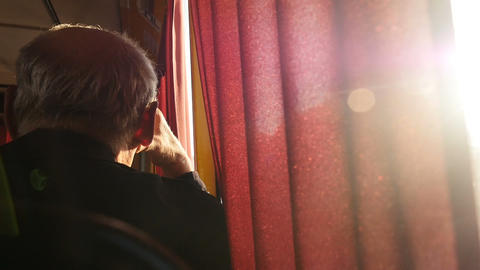 A man sits near a window in public transport. Bright rays of the sun. Close-up Live Action