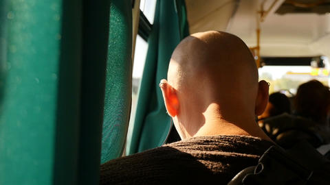 A bald man with earrings in his ear rides in public transport. Turned back. Slow Live Action