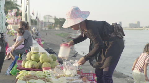 Woman street vendor on a street of Phnom Penh city, Cambodia, Asia Live Action