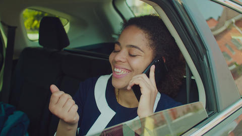 Businesswoman talking on cellphone in car backseat Live Action