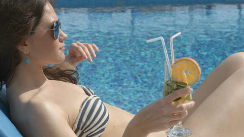 Sexy female enjoying cocktail on sunny beach, flirting, teasing Footage