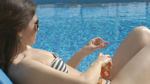 Pretty adult woman relaxing on beach, putting sunscreen on skin Footage