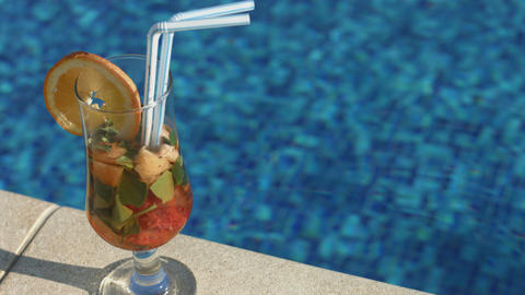 Closeup of cocktail on the pool deck. Vacation, resort, holiday Footage