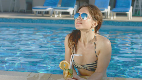 Pretty woman in bikini, sunglasses enjoys cocktail, pool party Footage