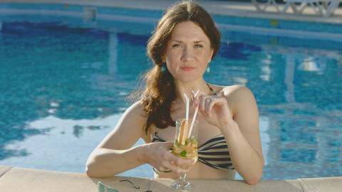 Pretty lady enjoying long drink in swimming pool, smiling at cam Footage