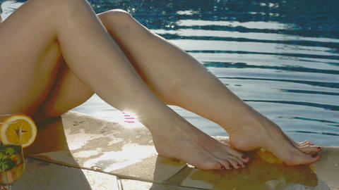 Sexy female legs splash water in pool, sun glitter, reflection Footage