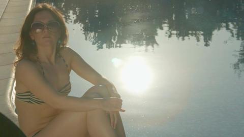 Single woman sitting near pool at sunset. Summer, magic hour Footage