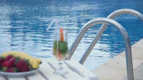 Refreshing summer cocktail, fruit near swimming pool, rack focus Footage