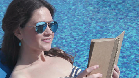 Young woman reading book near pool, enjoying summer sunshine Footage