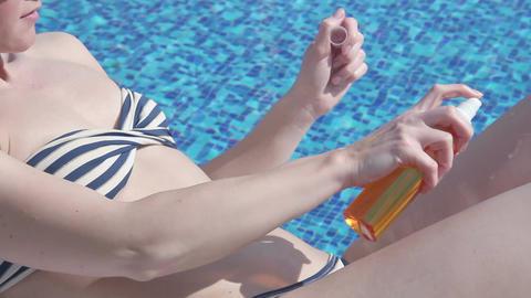 Pretty woman bikini applying tanning oil on skin, rubbing legs Footage