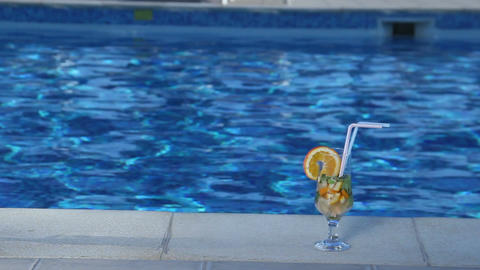 Closeup of fresh cocktail near swimming pool, alcoholic beverage Footage