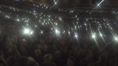 Stadium full of people waving hands, phone screens shine in darkness, love song Footage