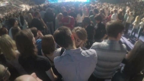 Happy couple kissing in crowd during love song at pop concert. Romantic proposal Footage