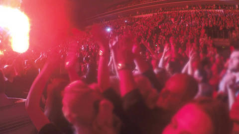 Fans applauding to popular band on brightly illuminated stage. Show on stadium Footage