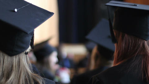 Female students in academic caps listening to lecture at graduation ceremony Footage