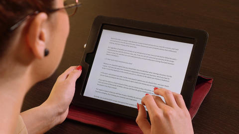 Young beautiful business woman sitting at a table and reading on tablet pc Footage