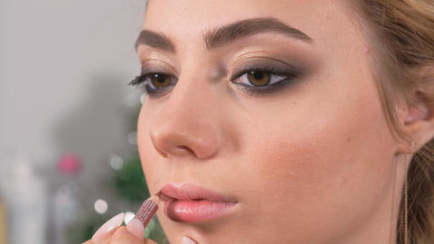 Applying makeup. The model's lips are painted with a makeup brush. Lip pencil Live Action