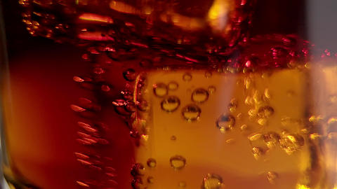 Ice cubes in a fresh cold glass of Cola - slow motion Live Action