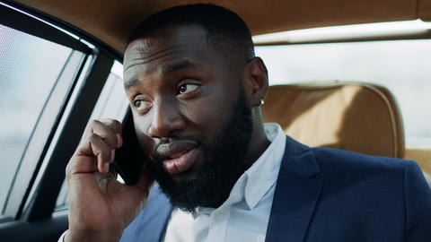 Tired african american man talking mobile phone in vehicle. Happy man face Live Action