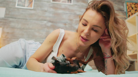 Cheerful woman in pajamas together with her little dog Live Action