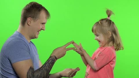 Father and little daughter playing rock paper scissors. Chroma Key. Leisure game Live Action