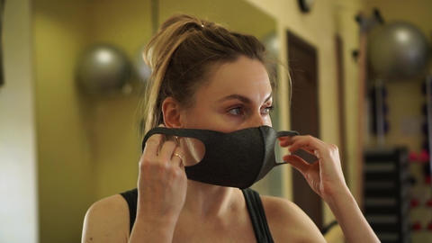 Caucasian beautiful female in sport wear put on two protective medical masks for double protection Live Action