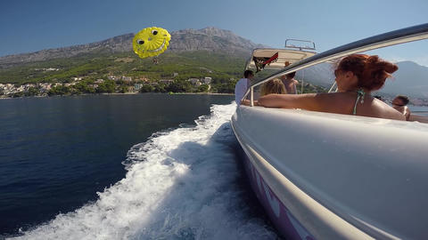Brela - Croatia - 09-08-2019- Parasailing big parachute smile face landing on deck of speed boat Live Action