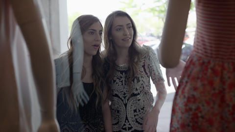 Twin teenage girls looking through window at mannequins Live Action