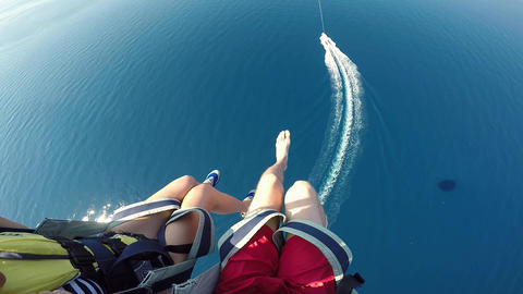 Young couple parasailing tied to speed boat over Adriatic sea Croatia action camera POV. Amazing Live Action