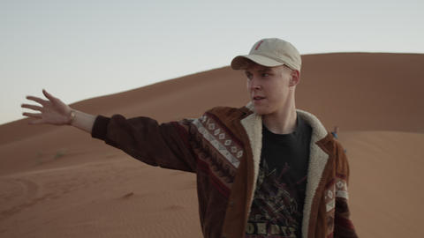 SLOW MOTION: ADVENTUROUS YOUNG MAN PICKING UP SAND FROM THE SAHARA DESERT IN Live Action