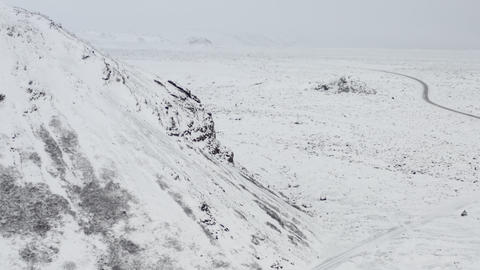 AERIAL: Towards Snow White Mountain with Black Rocks in Iceland Winter, Snowing Live Action