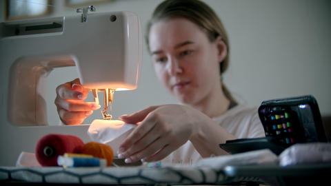 Young woman designer sewing a mask using a sewing machine Live Action