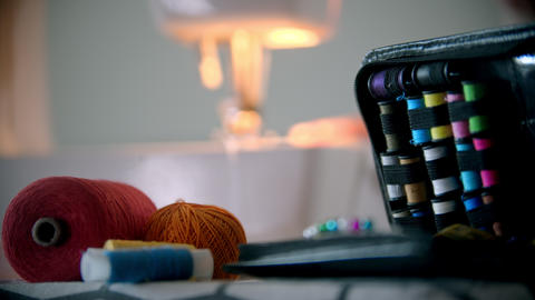 Young woman designer sewing using a sewing machine - sewing accessories on the Live Action