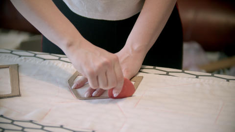 Young woman seamstress making marks using the soap and form indoors Live Action