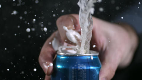 Rotating slow motion of aluminum can opening and spraying as tab is pulled Live Action