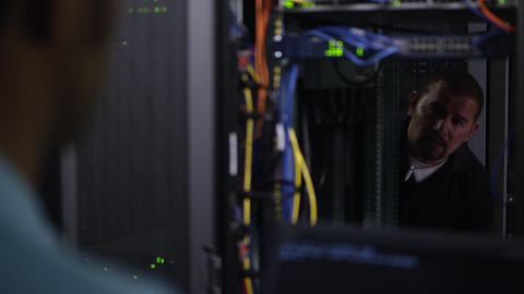 View through network rack of 2 men working on network server Live Action