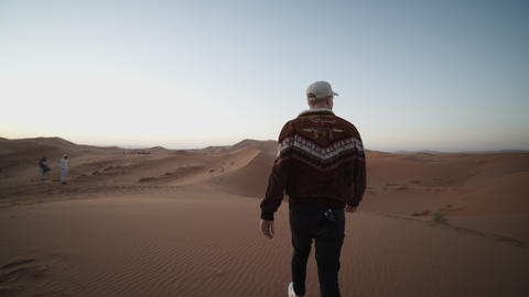 ADVENTUROUS YOUNG MAN WALKING TROUGH DESERT OVER DUNE AND PICKING UP SAND Live Action