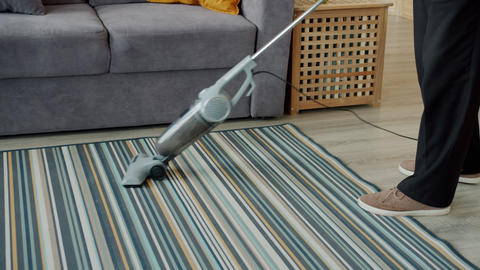 Slow motion of old man doing clean-up at home vacuuming carpet with vacuum Live Action