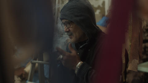 SLOW MOTION: OLD MAN SMOKING ON A CIGARETTE IN A FABRIC STORE IN OLD TOWN Live Action