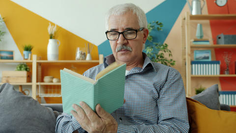 Intelligent old man in glasses reading book relaxing on couch at home alone Live Action