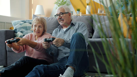 Slow motion of playful old people having fun with video game and talking in Live Action