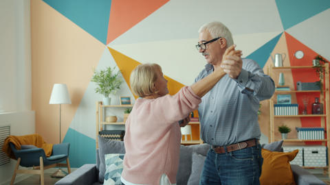 Cheerful pensioners dancing at home holding hands having fun with romantic music Live Action