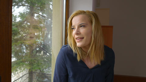 Young happy woman looking through the window and smiling Footage