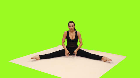 An attractive young woman doing pilates sitting on exercise mat, alpha channel Footage