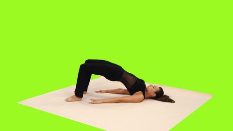 Slender brunette female doing yoga lying on exercise mat, alpha channel Footage